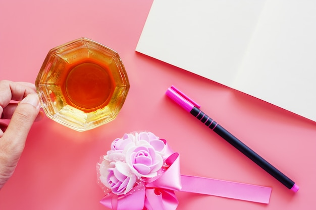 Cup of coffee with opened notebook, pen and flower bouquet on pink background