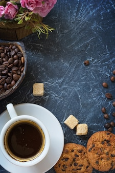 A cup of coffee with pieces of cane sugar, biscuits with chocolate and a vase with coffee beans.