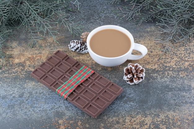 Una tazza di caffè con pigne e cioccolato. foto di alta qualità Foto Gratuite