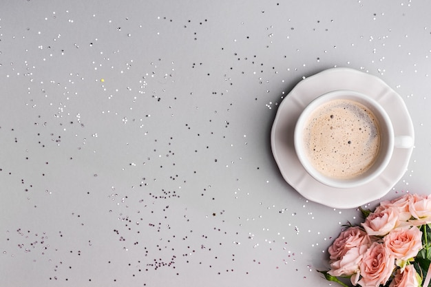 Cup of coffee with pink roses on a festive gray