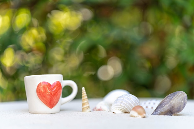 Cup coffee with red heart printed on sand against nature bokeh background.