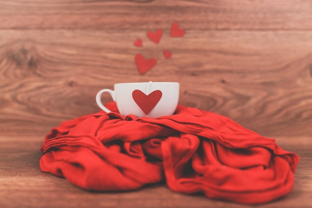 Cup of coffee with a red heart on a scarf