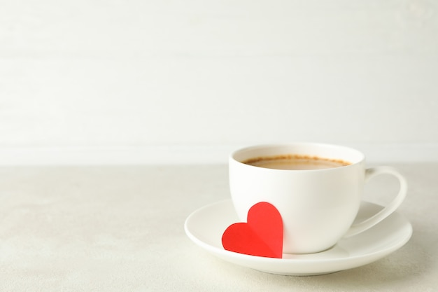 Cup of coffee with red heart on white textured table