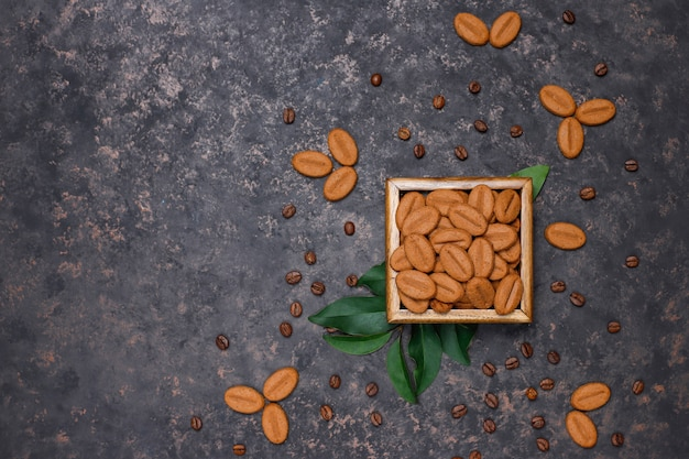 A cup of coffee with roasted coffee beans and coffee bean shaped cookies on dark surface