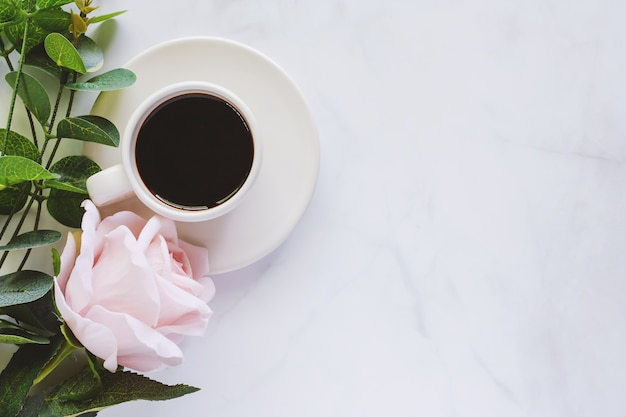 Cup of coffee with saucer and sweet pink rose on white marble background