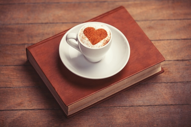 Cup of coffee with shape heart and book on a wooden table