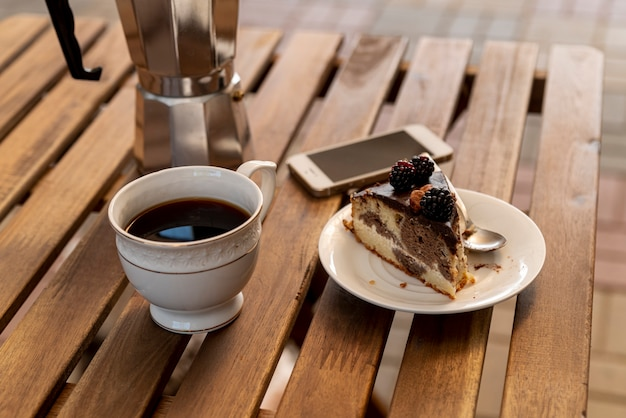 Cup of coffee with a slice of cake on table