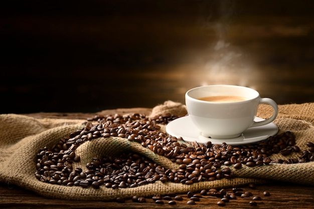 Cup of coffee with smoke and coffee beans on burlap sack on old wooden table