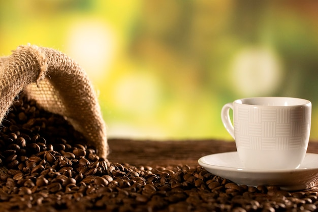 Cup of coffee with smoke and coffee beans in jute sack on coffee tree background.