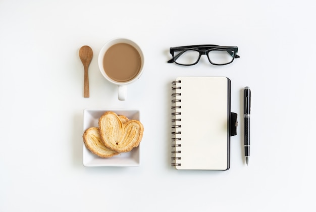 Cup of coffee with snacks and notebook on desk office with copy space