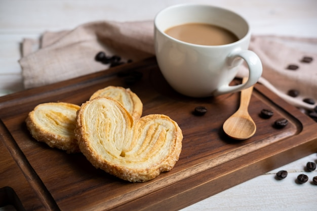 Cup of coffee with snacks on wooden cutting board on white wooden table