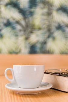 Cup of coffee with spectacles and book on wooden table