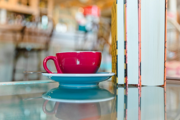 Cup of coffee with standing books on glass table