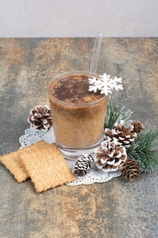Cup of coffee with tasty crackers and pinecones on marble background. high quality photo