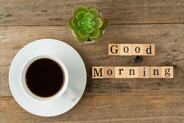 A cup of coffee with a text good morning on a shabby wooden board background flat lay