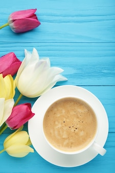 Cup of coffee with tulips on blue surface with copy space