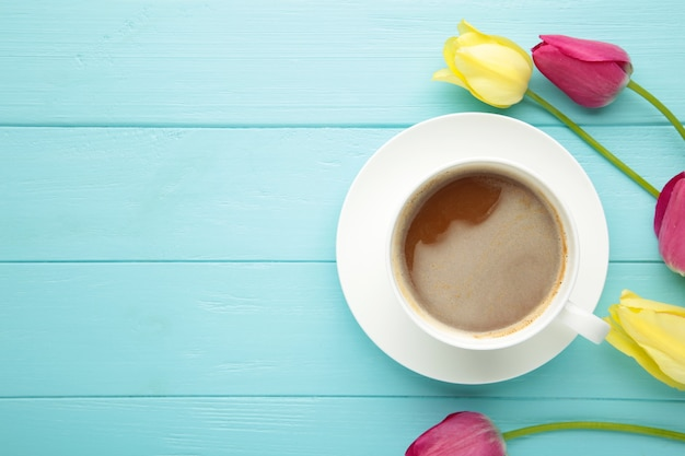Cup of coffee with tulips on blue surface