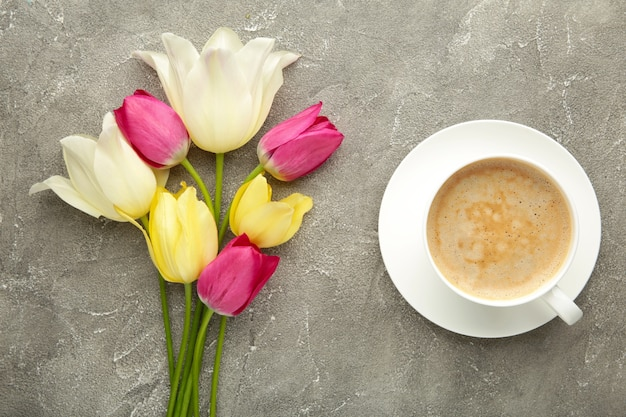 Cup of coffee with tulips on grey surface with copy space