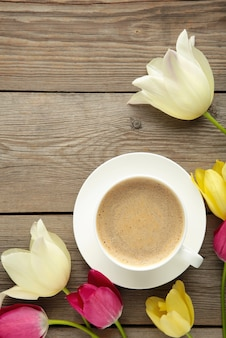 Cup of coffee with tulips on grey wooden surface