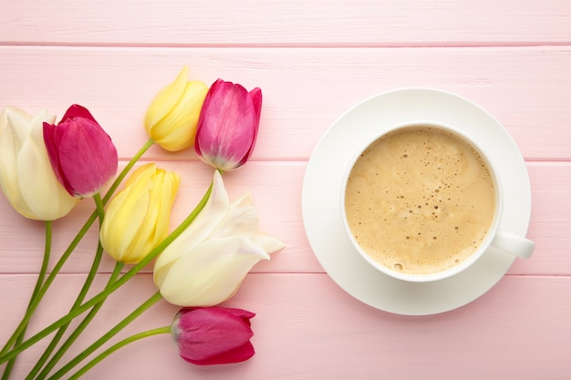 Cup of coffee with tulips on pink surface with copy space