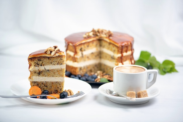 A cup of coffee with two pieces of sugar on a saucer and next to it a piece of carrot cake on a white plate, covered with caramel and decorated with nuts on top, in the background is a cake and a spri