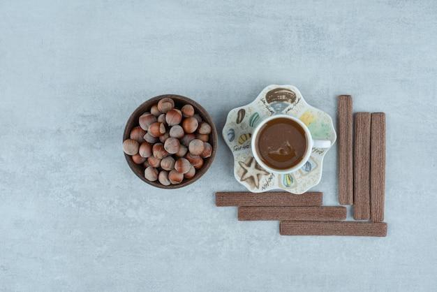Una tazza di caffè con vari dadi e biscotti