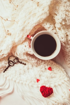 Cup of coffee with warm knitted scarf