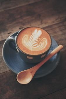 Tazza di caffè con un cucchiaio di legno su un tavolo di legno