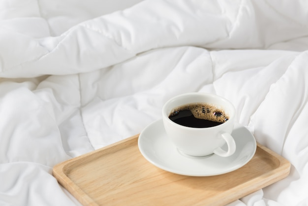Cup of coffee with wooden tray on bed
