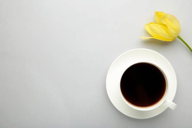 Cup of coffee with yellow tulip on grey surface with copy space