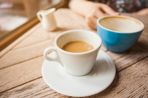 Cup of coffee on wooden table in cafeteria