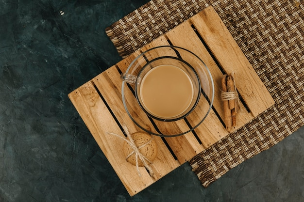 A cup of coffee on the wooden table in the dark blue background