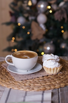 Cup of coffee on wooden table, decorative christmas tree,