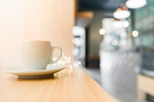 Cup of coffee on wooden table in restaurant