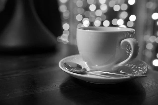 Cup of coffee on wooden table in tha cafe blur lights on background