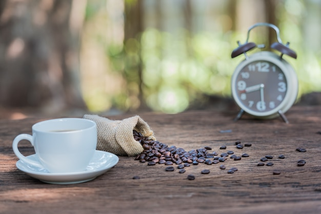 Cup of coffee on the wooden table with beans and alarm clock on green nature bokeh background.