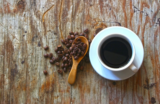 A cup of coffee on wooden table with coffee beans and wooden spoon