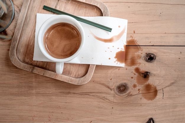 Cup of coffee on wooden table with coffee stains.