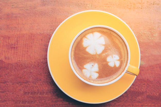Cup of coffee on wooden table with flower milk decoration on top of coffee surface