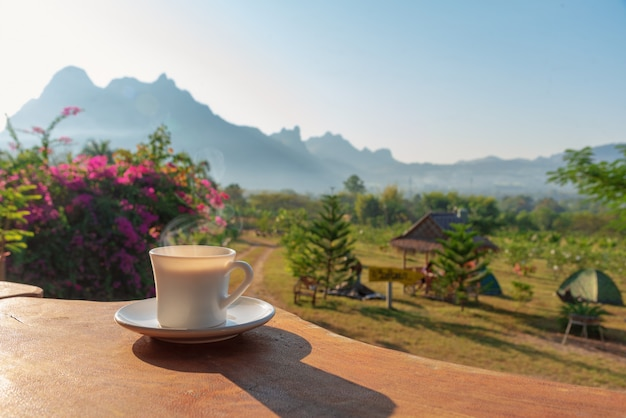Cup of coffee on wooden table with scenery of mountain and field of plants in background
