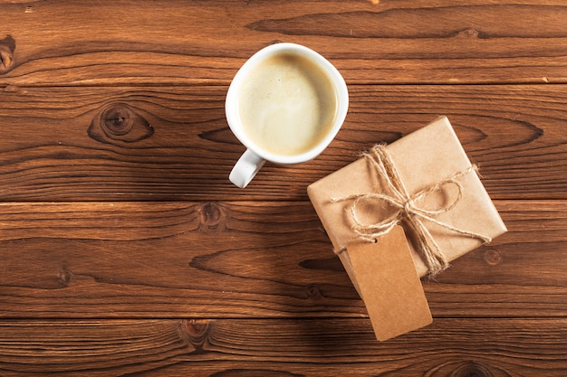 A cup of coffee and a wrapped gift on a wooden table
