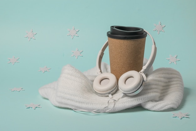 A cup of coffee wrapped in a scarf with snowflakes. winter mood.