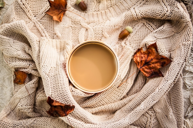 Cup of coffee wrapped in a woolen beige sweater