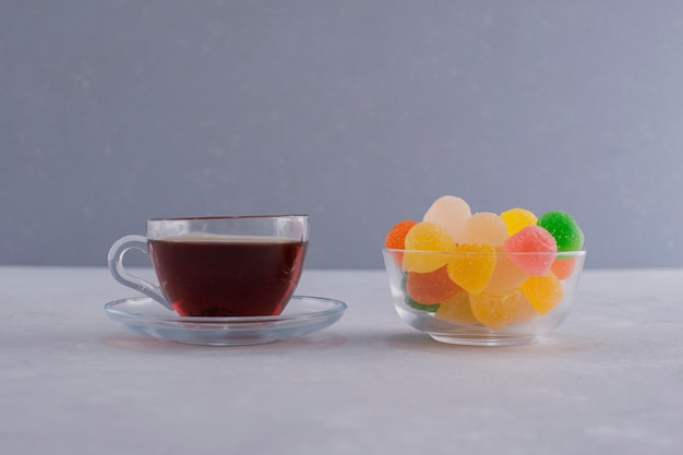 A cup of colorful marmelades with a glass of earl grey tea on blue.