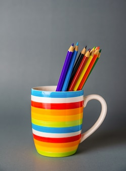 A cup colorful with pencils on gray