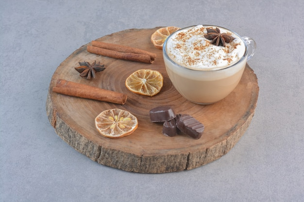 A cup of creamy coffee and cinnamon sticks on wood board.