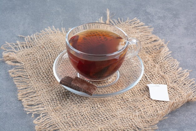 A cup of delicious aroma tea on sackcloth .