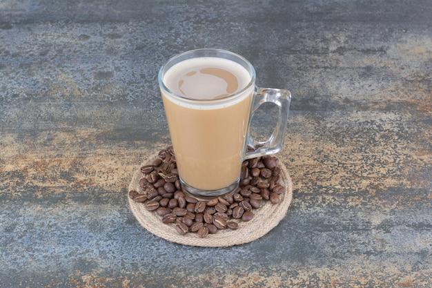 Una tazza di caffè delizioso con chicchi di caffè su sfondo marmo. foto di alta qualità