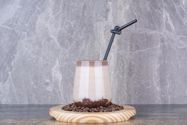 Una tazza di deliziosa bevanda con chicchi di caffè su marmo.