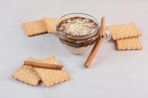 Una tazza di deliziosa bevanda con cracker e bastoncini di cannella